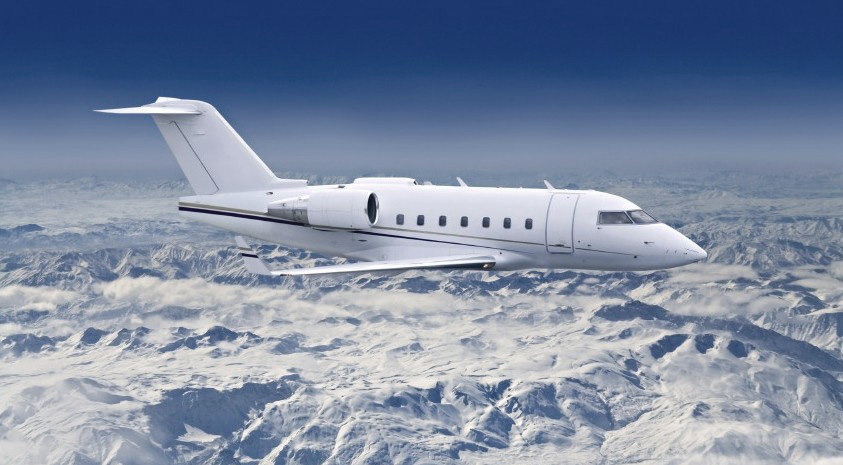 Private jet flying over snowy mountains
