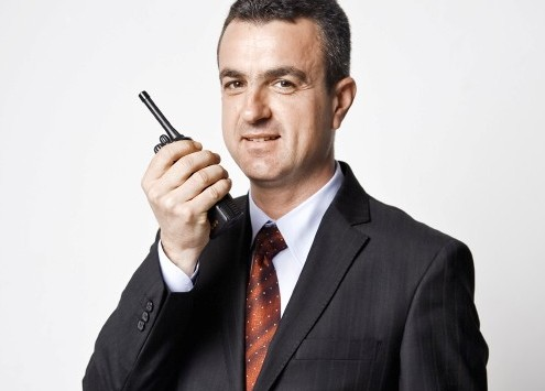 Man in suit holding radio